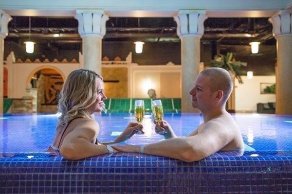 Mies ja nainen juomassa kuohuviiniä altaalla